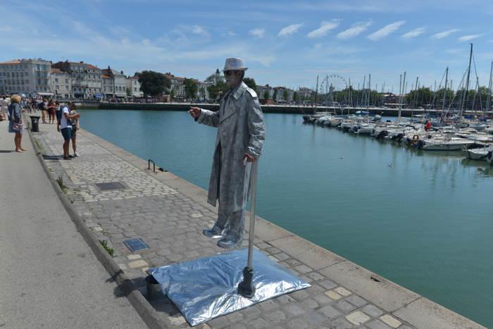 """""""Homme en suspension"""" sur sa canne sur le vieux port - La Rochelle"""