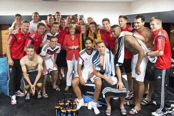 Angela Merkel dans le vestiaire des joueurs après leur victoire contre le Portugal   en prenant la pose (Coupe du Monde 2014)