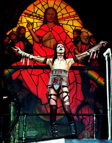 Marilyn Manson avec un vitrail représentant le Christ en arrière plan pendant un concert